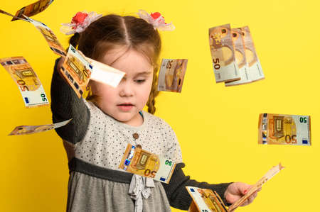 Little girl on a yellow background in the rain with money, euros flying in the air. new