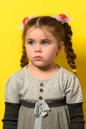 Beautiful little girl on a yellow background in meditation dreams of the new future.