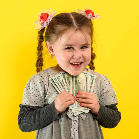 Children and financial responsibility, little girl on a yellow background with dollars in her hands, financial literacy in a child. new Stock fotó