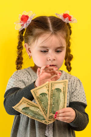 Happy child holding money, children's joy in a lot of money, portrait of a girl on a yellow background. new
