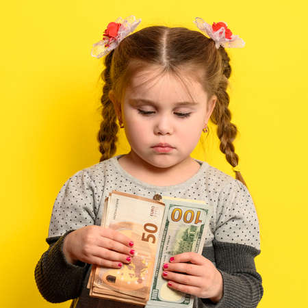 Financial security of the child, the girl holds money in hands, a portrait of the child on a yellow background. new Stock fotó