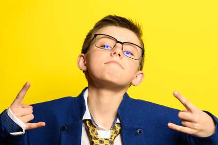 Attractive boy in an adult suit on a yellow background, a child's imagination about adult life. new Stock fotó