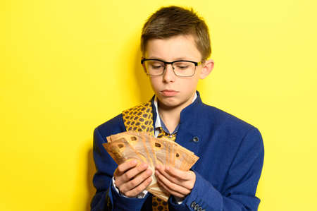 An 11-year-old boy in an adult and oversized suit holds a euro, a portrait of a child with money on a yellow background. new Stock fotó