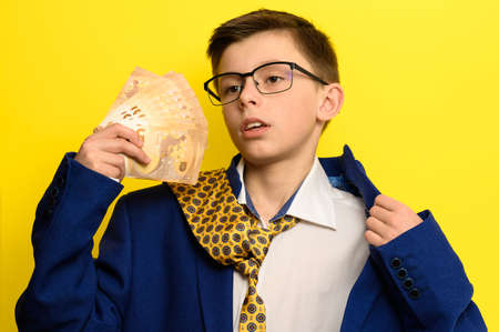 A child with a pathetic look holds in his hands euro bills, a boy in an adult suit on a yellow background, a blue jacket and a yellow tie. new