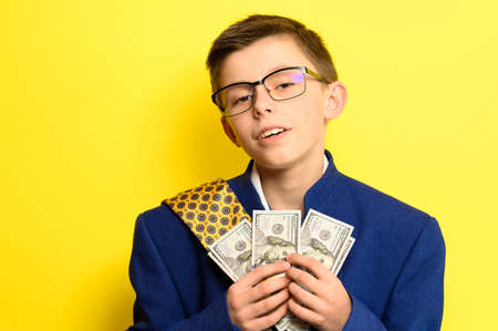 A boy in glasses and an oversized suit with a satisfied face is holding US dollars, a child and big money. new