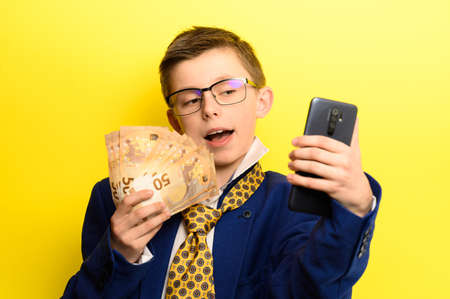 Boy in a big suit, selfie on a yellow background with money. new