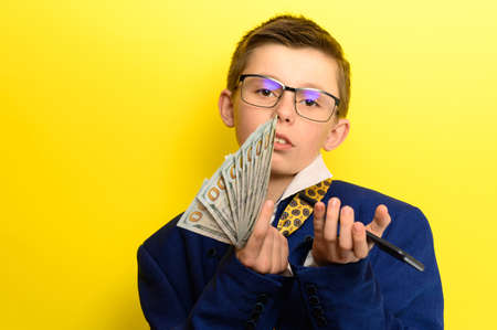 Successful and rich child taking a selfie with money, portrait of a boy in a suit on a yellow background. new