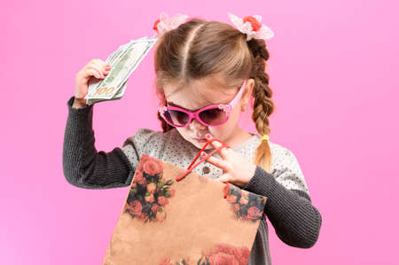 Little girl in glasses with a package and money on a pink background, child and shopping. new