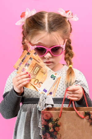Little cute girl on a pink background with a bag and money, the theme of shopping with children. new