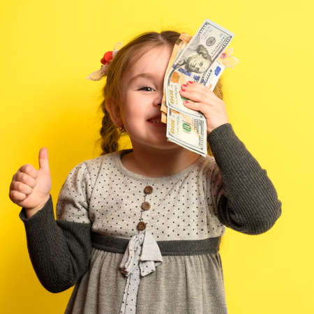Caucasian girl holding money, portrait of a child on a yellow background, financial literacy of children. new