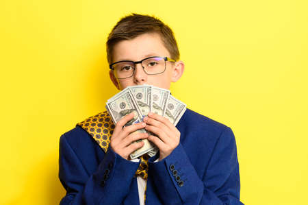 Not a lot of adult child, financially literate boy, money in the hands of a child, portrait on a yellow background. new