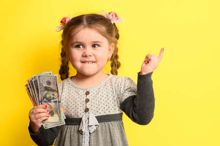 Caucasian girl holding money, portrait of a child on a yellow background, financial literacy of children. new Stock Photo