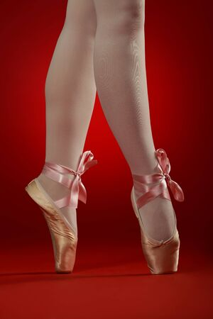 tiptoes: ballerinas crossed legs with ballet shoes on red background with satin cord