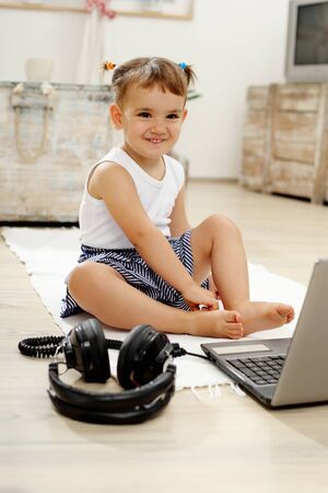 southern european descent: little girl playing with laptops and headset in the living room