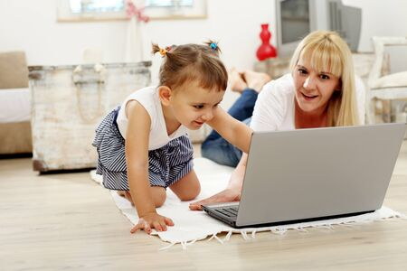 southern european descent: Mother and Daughter Using Laptop Computer Lying on Floor