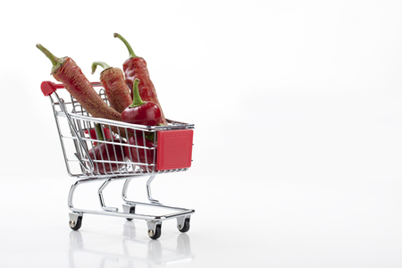 carro supermercado: Red hot chili peppers in supermarket trolley isolated on white