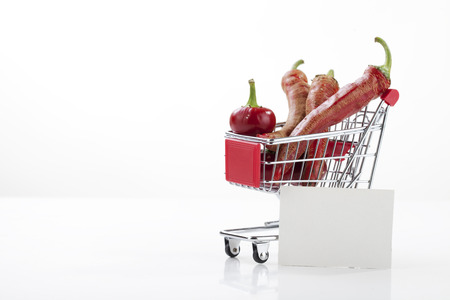 supermarket trolley: Red hot chili peppers in supermarket trolley isolated on white