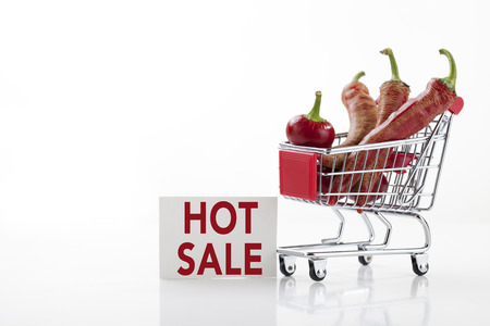 supermarket trolley: Red hot chili peppers in supermarket trolley and hot sale sign, isolated on white Stock Photo