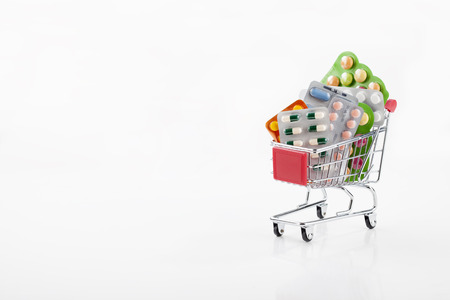 supermarket trolley: Drugs and pills in supermarket trolley isolated on white Stock Photo