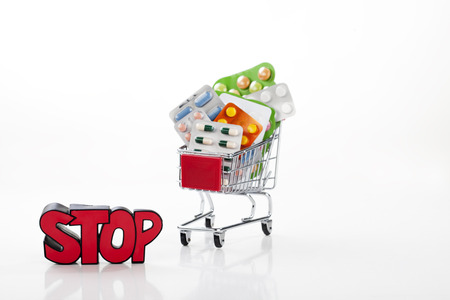 supermarket trolley: Drugs and pills in supermarket trolley with sign stop, isolated on white