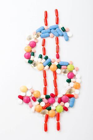 signo de pesos: Las píldoras y tabletas en el fondo blanco con el símbolo del dolar en colores vivos
