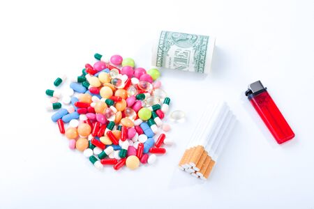 Cigarettes, colorful pills and tablets with dollar bill on a white background in the studio tabletop. Stop smoking