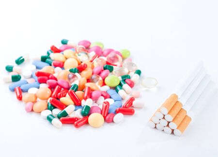 Cigarettes colorful pills and tablets on a white background in the studio tabletop.stop smoking Stock Photo