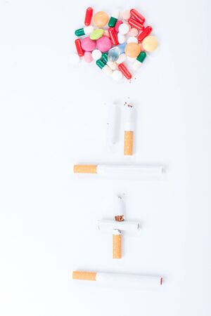 Cigarettes colorful pills and tablets on a white background in the studio tabletop. Stop smoking concept Stock Photo