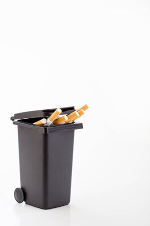 fetid: Bunch of cigarettes in the black trash canon white background. Quit smoking concept