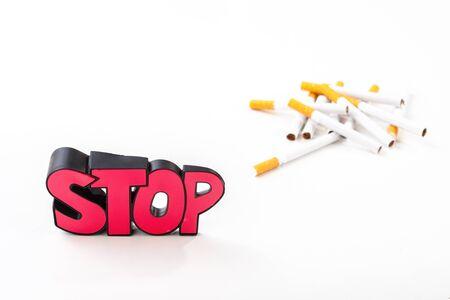 sustancias toxicas: Dejar de fumar concepto, manojo de cigarrillos en el fondo blanco con una señal de stop roja