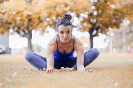 Young woman practicing yoga in the park on the green grass with fallen leaves in autumn with blurred background. Shallow depth of field, vintage image