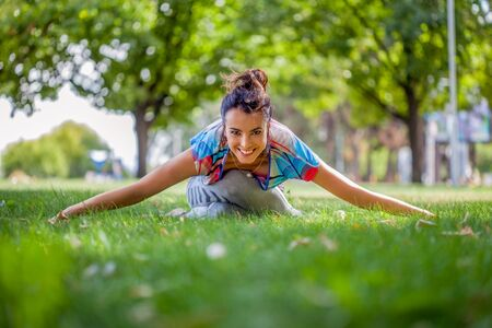 Young woman practicing yoga in the park on the green grass with fallen leaves in autumn with blurred background. Shallow depth of field Stock Photo