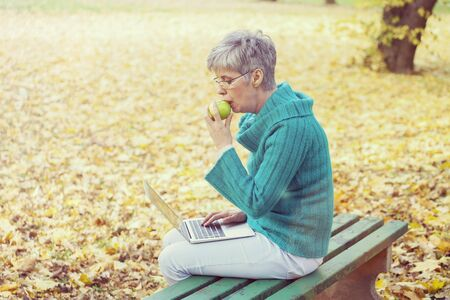 Older woman with gray hair in a park with a gray computer sits on a chair in the autumn outdoor ambience