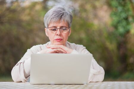 conceived: Older woman with gray hair in a park with a gray computer sits on a chair in the autumn outdoor ambience