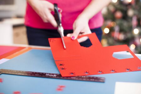 Young woman make scrapbook of the papers on the table using antique tools for cutting paper. Hand made photo album.Shallow depth of field