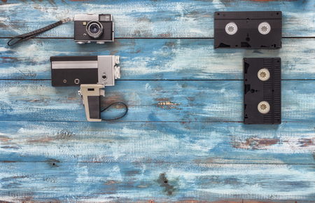 videocassette: Video and photo cameras, audio cassettes, VHS video tapes on a blue old vintage background. Photographed in retro style Foto de archivo