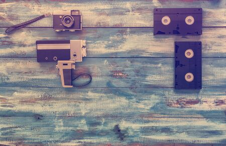 videocassette: Video and photo cameras, audio cassettes, VHS video tapes on a blue old vintage background. Photographed in retro style Stock Photo