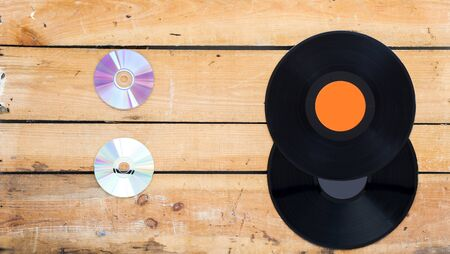 facing each other: Vinyl records and compact disc on a vintage background facing each other
