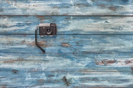 videocassette: Photo camera on a blue old vintage wooden blue background. Photographed in retro style