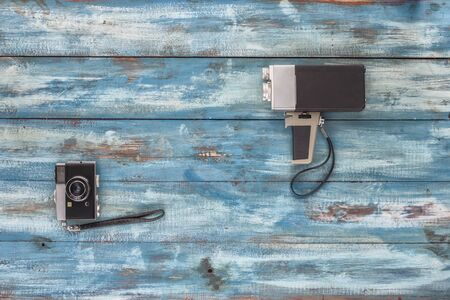 videocassette: Video and photo camera on a blue old vintage blue background. Photographed in retro style Stock Photo