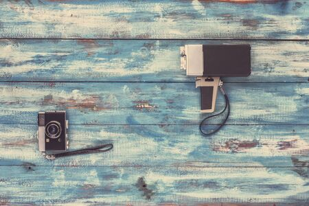videocassette: Video and photo camera on a blue old vintage blue background. Photographed in retro style Foto de archivo