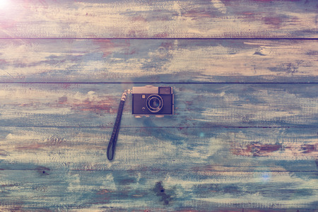 cinematographer: Photo camera on a blue old vintage wooden blue background. Photographed in retro style