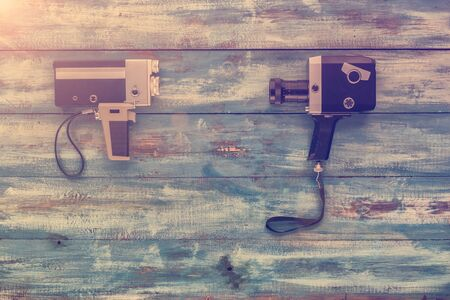 videocassette: Video camera on a blue old vintage blue background. Photographed in retro style