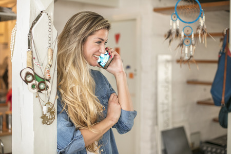 Beautiful young woman in a hipster kitchen talks to her phone dressed in a jeans shirt and a white shirt 스톡 콘텐츠
