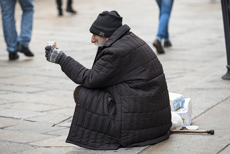 mendicant: Milan Italy 12142015: Milan as the other big cityes in the world presents big contrasts between the richness and the joy for the holidays and chrismats the poorness of the tramps asking alms.