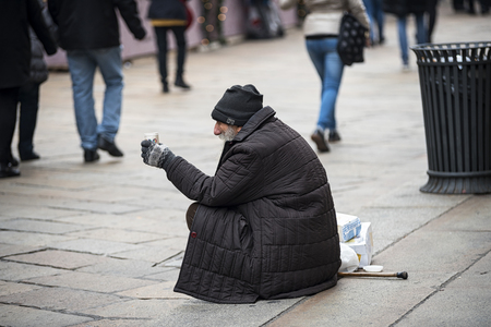 poorness: Milan Italy 12142015: Milan as the other big cityes in the world presents big contrasts between the richness and the joy for the holidays and chrismats the poorness of the tramps asking alms.