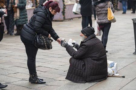 ミラノ 12142015: 世界の他の大きな cityes としてミラノは、休日や chrismats 施しを求めて路上の貧しさのため大きなコントラストの豊かさと喜びの間を提示します。 写真素材 - 50392222