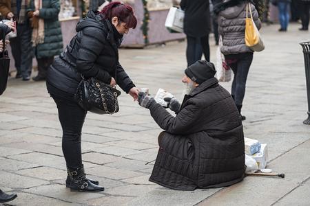 Milano Italia 12142015: Milano come gli altri grandi Comuni in tutto il mondo presenta grandi contrasti tra la ricchezza e la gioia per le vacanze e chrismats la povertà dei barboni che chiedono l'elemosina. Archivio Fotografico - 50392222