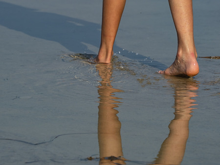 Girls legs reflection in the water