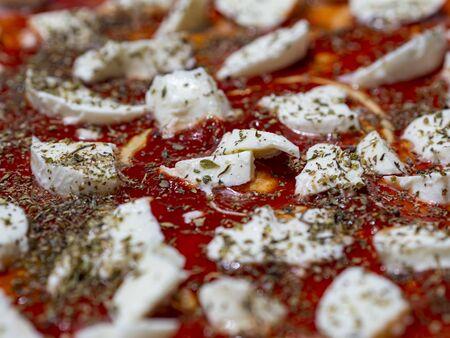 Mozzarella tomato and oregano detail on a raw pizza Archivio Fotografico - 131975839